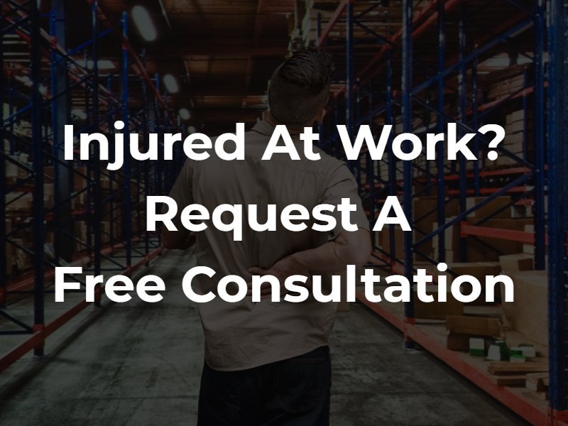 "A man in a warehouse holding his back in pain with the text ""Injured at work? Request a free consultation"" superimposed"